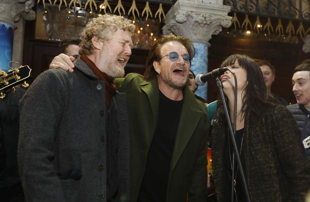 (left to right) Glen Hansard, Bono and Imelda May take part in the annual Christmas Eve busk on Grafton Street, Dublin (Lorraine O'Sullivan/PA)