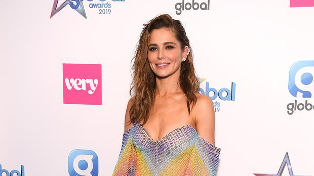 Cheryl sports crop top and thigh-high boots as she promotes