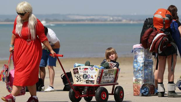 Festival goer Dylan Porter, two, from Portsmouth, is pulled along in a wagon by his mum upon arriving in Ryde, on the Isle of Wight