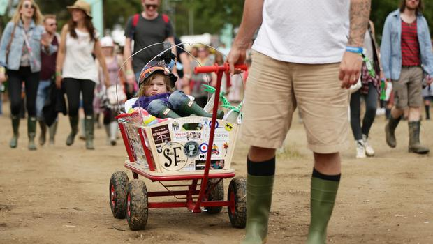 Dylan Porter, aged two, from Portsmouth, is pulled along in a wagon by his dad at the Isle of Wight Festival