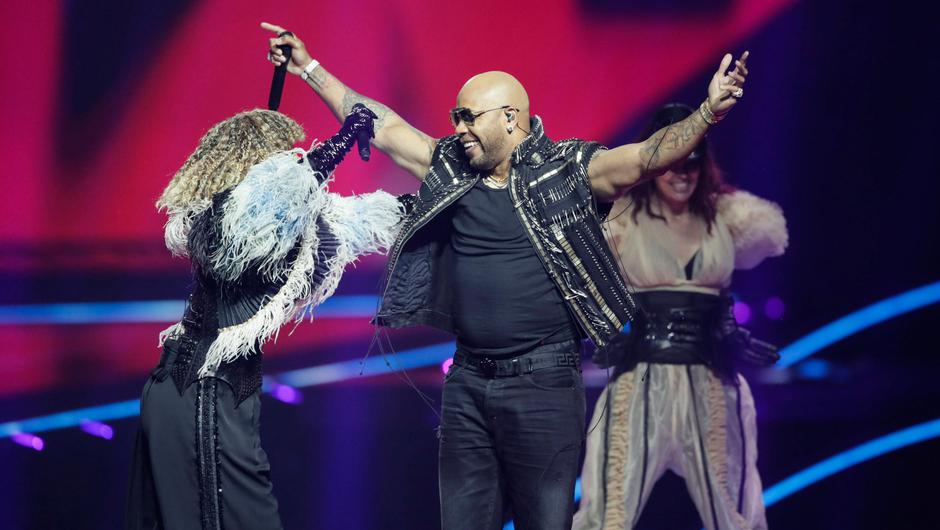 Senhit, left, from San Marino embraces rapper Flo Rida at the second semi-final of the Eurovision Song Contest at Ahoy arena in Rotterdam, Netherlands, Thursday, May 20, 2021. (AP Photo/Peter Dejong)