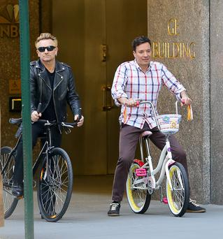 Bono and Jimmy Fallon seen riding their bikes on sidewalk while filming a set for 'The Tonight Show Starring Jimmy Fallon' in New York City