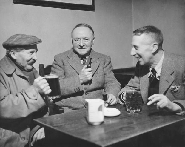 English composer and author Sir Arnold Bax (1883 - 1953, centre), Master of the King's Music, enjoys a lunchtime drink at the White Horse Hotel in Storrington, Sussex, with Taffy (left), a local man, and Stanley Fitch (right), the proprietor of the hotel,
