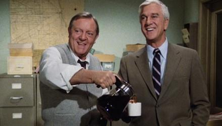 Captain Hocken (Alan North) pours Frank Drebin (Leslie Nielsen) a coffee in a fake freeze-frame from the hilarious Police Squad!