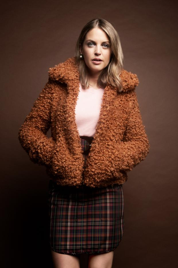 Amy wears: Toffee brown teddy jacket, €113, River Island; Pink jumper, €110, Pinko, Harvey Nichols; Plaid skirt with velvet buckle, €195, Sandro, Brown Thomas; Vintage green & pearl clip-on earrings, €25, Rhinestones. Photo: Barry McCall