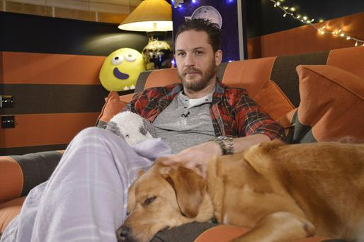 For use in UK, Ireland or Benelux countries only Undated BBC handout photo of Tom Hardy as he cuddles up to his dog for his new role - as a bedtime storyteller on CBeebies.
