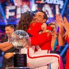 Claudia Winkleman (left) and Tess Daly (right) present Katya Jones and Joe McFadden with the glitterball trophy after they won the final of the BBC 1 show Strictly Come Dancing (BBC/PA)
