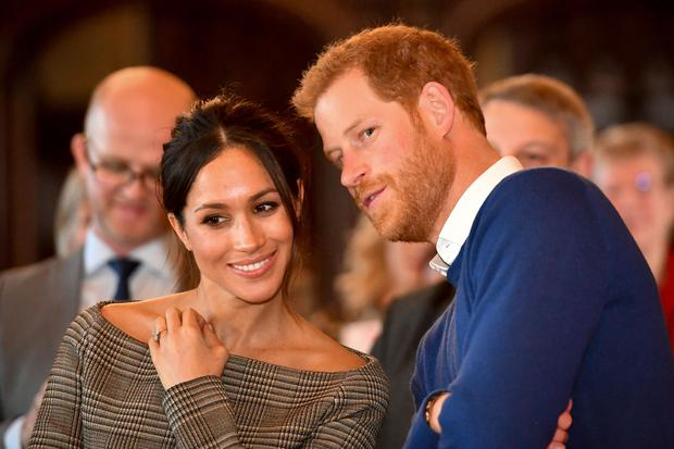 Prince Harry whispers to Meghan Markle as they watch a dance performance in Cardiff (Ben Birchall/PA)