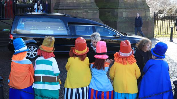 Children dressed as Diddymen watch the funeral cortege leave (Peter Byrne/PA)