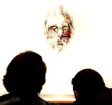 Viewers look at a Louis Le Brocquy portrait of WB Yeats.
