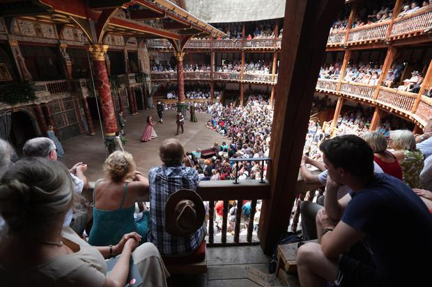 Audience members watch a production of 'A Midsummer Night's Dream' in Shakespeare's Globe theatre on the banks of the River Thames in London in 2013. Photo: Getty Images