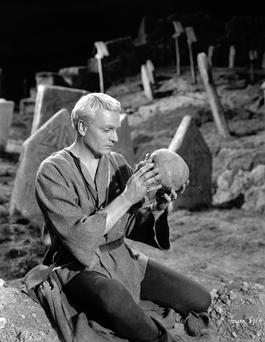 Laurence Olivier's Hamlet kneels in the graveyard with Yorrick's skull in his hands in a 1948 film adaptation.