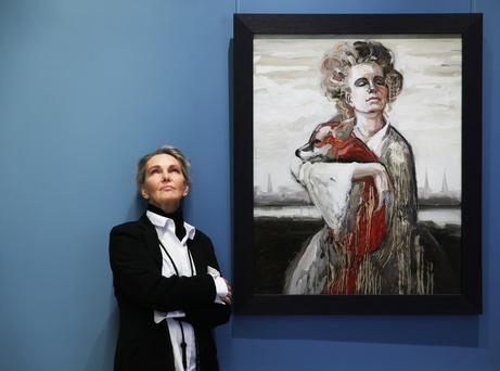 Zane Sutra stands beside her portrait in the National Gallery of Ireland as part of the Hennessy Portrait competition. Photo: Leon Farrell