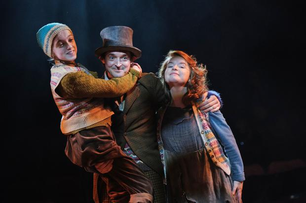 Niamh Moriarty as Tiny Tim, Hugh O'Conor as Bob Cratchit, and Catriona Ennis as Mrs Cratchit in A Christmas Carol at the Gate