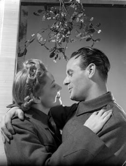 30th November 1939: An Auxiliary Fire Servicewoman and a British Army private kissing under the mistletoe. (Photo by Fox Photos/Getty Images)