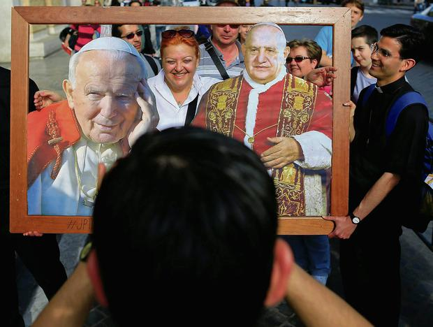 Faithful pose with pictures of the canonised popes in Rome