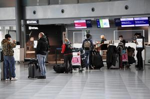 Passengers wearing protective face masks practice social distancing as they queue for the customer service at the Helsinki International Airport in Vantaa, Finland May 13, 2020.   Lehtikuva/Vesa Moilanen via REUTERS