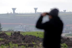 "A journalist uses a pair of binoculars to look at the Altiplano Federal Penitentiary, where the drug lord Joaquin ""El Chapo"" Guzman escaped from"