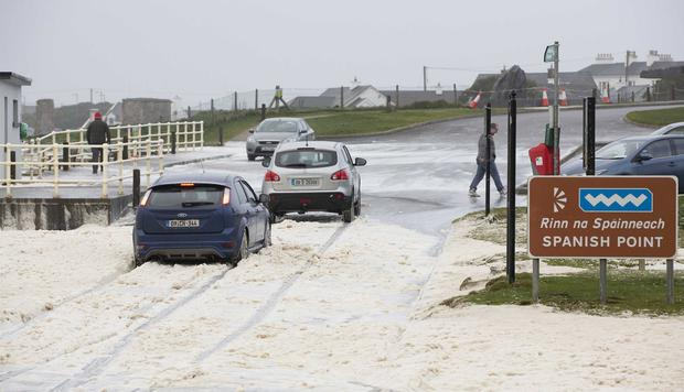 Surf's up: Cars drive through surf froth at Spanish Point in Co Clare. Photo: Press 22