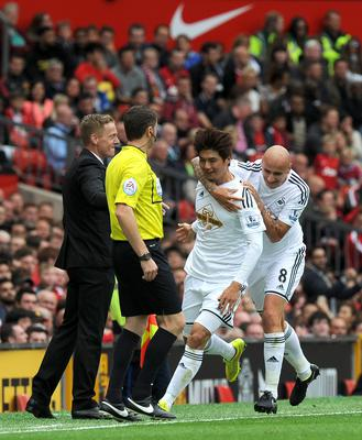 Swansea City's Ki Sung-yueng celebrates scoring his side's first goal of the game with teammate Jonjo Shelvey (right) and manager Gary Monk (left) during the Barclays Premier League match at Old Trafford