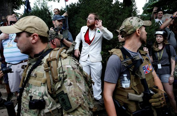 A white supremacists stands behind militia members after he scuffled with a counter demonstrator in Charlottesville, Virginia, U.S., August 12, 2017. REUTERS/Joshua Roberts