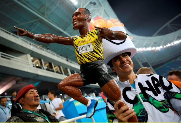 Fans hold a figure of Usain Bolt (JAM) of Jamaica in the stands after Bolt won the gold medal in the men's 100m final