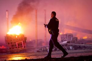 A police officer walks by a blaze, Monday, April 27, 2015, after rioters plunged part of Baltimore into chaos, torching a pharmacy, setting police cars ablaze and throwing bricks at officers. (AP Photo/Matt Rourke)
