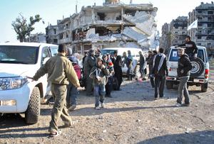 Aid teams evacuated hundreds of exhausted civilians from besieged districts of the city of Homs, as Syria's regime and rebels again accused each other of violating a truce.