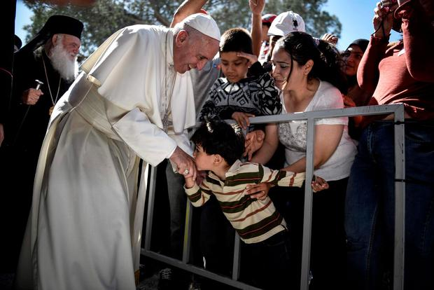A child kisses the hand of Pope Francis, during a visit at the Moria refugee camp on the island of Lesbos, Greece. (Andrea Bonetti/Greek Prime Minister's Office via AP)