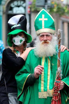 A woman in a face mask takes a picture with a man dressed as St Patrick near the Temple bar in Dublin, on St Patrick's day. PA Photo. Picture date: Tuesday March 17, 2020. See PA story HEALTH Coronavirus. Photo credit should read: Niall Carson/PA Wire
