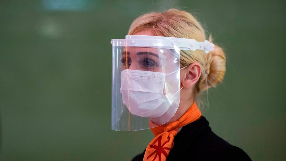 A member of Charles de Gaulle airport personnel wears a protective face mask and visor. (Photo by Ian LANGSDON / EPA POOL / AFP)
