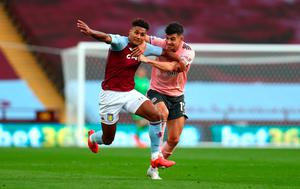 GRAPPLING: Sheffield United's John Egan wrestles with Ollie Watkins of Aston Villa for which he was later shown a red card following a VAR review at Villa Park