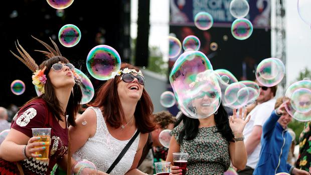 Festival goers playing with soap bubbles at the Isle of Wight Festival, in Seaclose Park, Newport, Isle of Wight. PRESS ASSOCIATION Photo. Picture date: Sunday June 14, 2015. Photo credit should read: Yui Mok/PA Wire