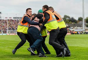 A Mayo supporter is restrained by security staff after he tries to confront referee Cormac Reilly during the closing stages of the Semi-Final Replay between Kerry and Mayo. Picture credit: Diarmuid Greene / SPORTSFILE
