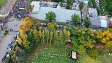 Relatives and friends bury the remains of Diego Maradona while police keep fans outside the Jardin de Bellavista cemetery in Buenos Aires, Argentina.. (AP Photo/Rodrigo Abd)