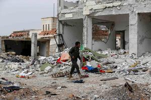 A fighter of the Kurdish People's Protection Units (YPG) walks past damaged buildings in the northern Syrian town of Kobani January 28, 2015.  REUTERS/Osman Orsal