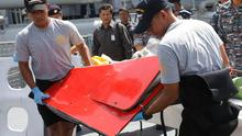 Crew members of an Indonesian navy ship carry what could be the tail of a missing AirAsia jet. It is in this part of the plane that the crucial black box voice and flight data recorders are located. AP Photo/Trisnadi