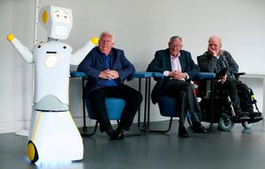 IrelandÕs first socially assistive AI robot 'Stevie II' from robotics engineers at Trinity College Dublin is unveiled during a special demonstration at the Science Gallery in Dublin, as Mick McCarthy (left) Tony McCarthy (centre) and Brendan Crean, who all helped trial the robot through the charity ALONE look on. Brian Lawless/PA Wire