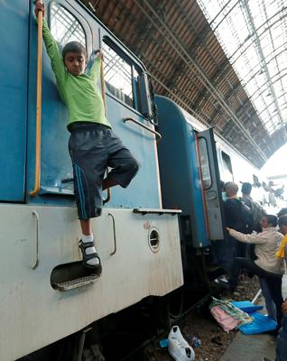 Migrants try to board a train at the railway station in Budapest, Hungary, Thursday, Sept. 3, 2015. Over 150,000 migrants have reached Hungary this year, most coming through the southern border with Serbia, and many apply for asylum but quickly try to leave for richer EU countries.(AP Photo/Frank Augstein)