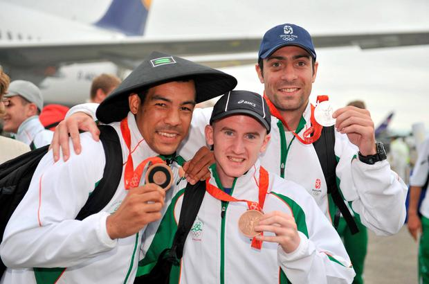 The Irish Olympic Team, including silver medallist Kenny Egan, left, bronze medallist Darren Sutherland, right, and bronze medallist Paddy Barnes, arrive at Dublin Airport, Dublin Picture credit: David Maher / SPORTSFILE