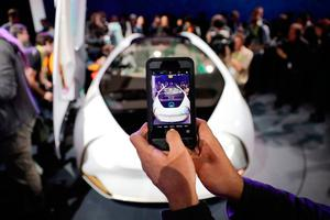 An attendee uses his phone to photograph the Toyota Concept-i during a news conference at CES International, Wednesday, Jan. 4, 2017, in Las Vegas. (AP Photo/Jae C. Hong)