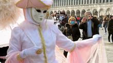 Different roles: Tourists wear protective masks in Venice as they watch and photograph a Carnevale reveller in St Mark's Square. Photo: REUTERS/Manuel Silvestri