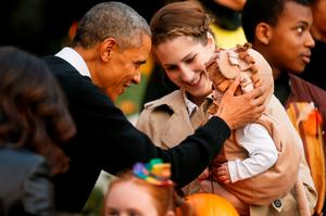 U.S. President Barack Obama (2nd L) and first lady Michelle Obama (L, obscured) greet children on the South Lawn for a Halloween trick-or-treating celebration in Washington. Invitees included local children and the children of military families, according to the White House (REUTERS/Jonathan Ernst)