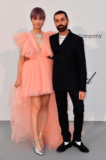 Chinese actress and singer Li Yuchun (L) and Italian fashion designer Giambattista Valli pose as they arrive on May 23, 2019 at the amfAR 26th Annual Cinema Against AIDS gala at the Hotel du Cap-Eden-Roc in Cap d'Antibes, southern France, on the sidelines of the 72nd Cannes Film Festival. (Photo by Alberto PIZZOLI / AFP)