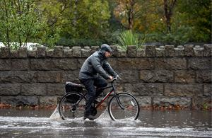 Cyclist driving through floods on Clontarf road