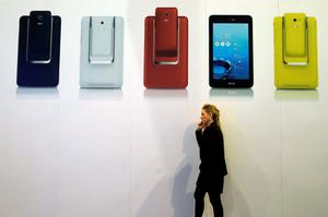 A visitor talks on a mobile phone in front of an advertising panel at the Mobile World Congress in Barcelona