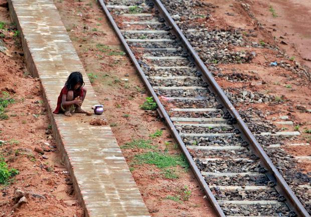 A girl plays with clay next to a railway track on a hot summer day in Agartala, India. REUTERS/Jayanta Dey