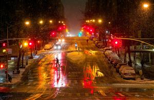 A person crosses a snow-covered street in the Upper West Side neighborhood of New York, Monday, Jan. 26, 2015  (AP Photo/Craig Ruttle)