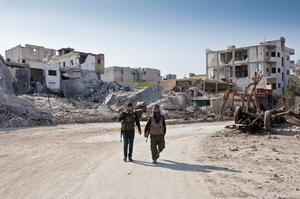 In this Wednesday, Nov. 19, 2014 photo, Kurdish People's Protection Units (YPG) soldiers walk near the town entrance circle heading to their strongholds in Kobani, Syria. (AP Photo/Jake Simkin)
