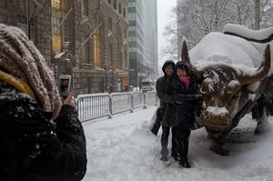 Tourists pose for a photo with the Charging Bull during a morning snow in New York's financial district near Wall Street